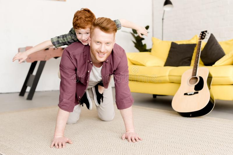 ευτυχείς redhead πατέρας και γιος που χαμογελούν στη κάμερα ενώ έχοντας τη διασκέδαση από κοινού στοκ φωτογραφίες