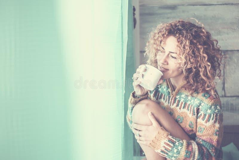 Ευτυχισμένη ήσυχη και γαλήνια νέα ελκυστική γυναίκα απολαύστε την ώρα χαλάρωσης στο σπίτι πίνοντας ένα φλιτζάνι τσάι και κοιτώντα στοκ εικόνες