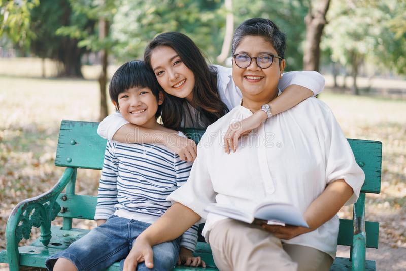 Ευτυχισμένη ασιατική οικογένεια με τη μητέρα γιαγιά και το γιο να κάθονται στον πάγκο, ενώ η μητέρα τους αγκάλιαζε και τους δύο σ στοκ εικόνες