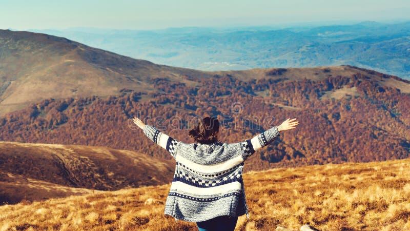 Ευτυχισμένη γυναίκα πάνω από βουνά με ανοιχτά χέρια Ελευθερία και υγιεινός τρόπος ζωής Όμορφο φθινοπωρινό τοπίο Επιτυχημένη γυναί στοκ φωτογραφίες