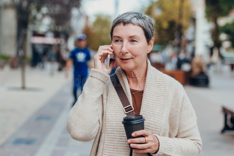 Ευτυχισμένη γυναίκα στους δρόμους της πόλης που χρησιμοποιεί κινητό τηλέφωνο με ένα ποτήρι καφέ στα χέρια της στοκ φωτογραφίες
