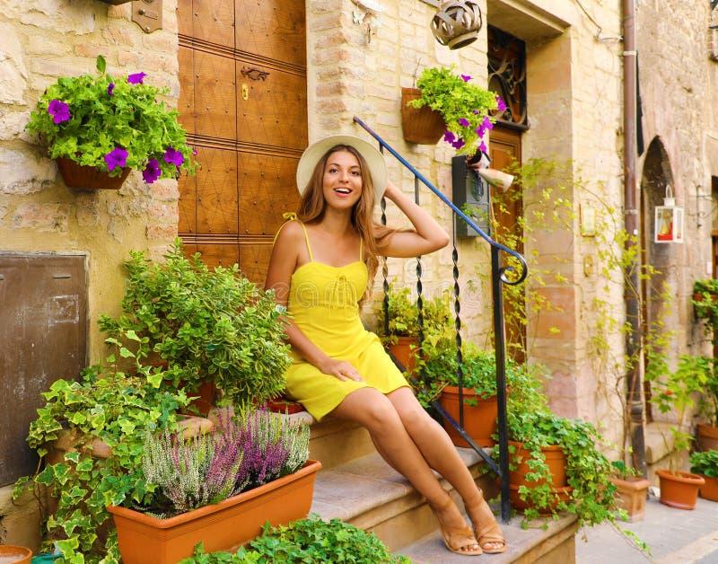 Ευτυχισμένη όμορφη γυναίκα που κάθεται στα σκαλιά σπίτι ανάμεσα σε πολύχρωμα λουλούδια και φυτά σε μια μικρή ιταλική πόλη στοκ εικόνες με δικαίωμα ελεύθερης χρήσης