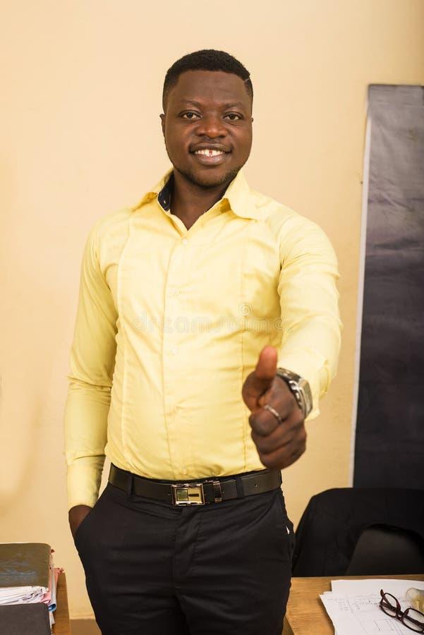 Ευτυχισμένος επιχειρηματίας στο γραφείο κάνει χειρονομία στοκ εικόνα