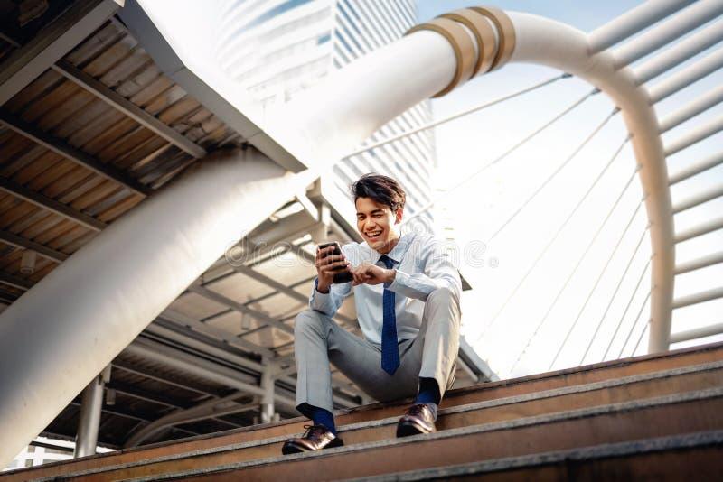 Ευτυχισμένος νεαρός επιχειρηματίας που κάθεται στη σκάλα και χρησιμοποιεί smartphone Αστικός τρόπος ζωής Προβολή χαμηλής γωνίας Η στοκ φωτογραφίες με δικαίωμα ελεύθερης χρήσης