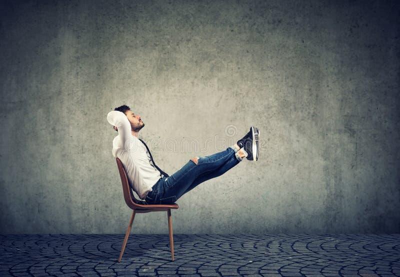 Ευτυχισμένος περιστασιακός επιχειρηματίας που κάθεται στην καρέκλα με τα πόδια να χαλαρώνουν στοκ εικόνες