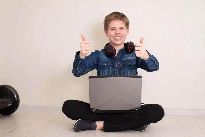 Ευτυχισμένο έφηβο αγόρι με φορητό υπολογιστή και ακουστικά που δείχνουν κίνηση με τους αντίχειρες στο πάτωμα ενώ κάθεται στο πάτω στοκ εικόνες με δικαίωμα ελεύθερης χρήσης