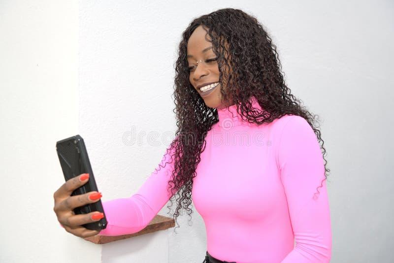 Ευτυχισμένο μαύρο κορίτσι με μακριά μαύρα μαλλιά Χαμογελά ενώ φωτογραφίζει με το τηλέφωνό της στοκ φωτογραφία με δικαίωμα ελεύθερης χρήσης