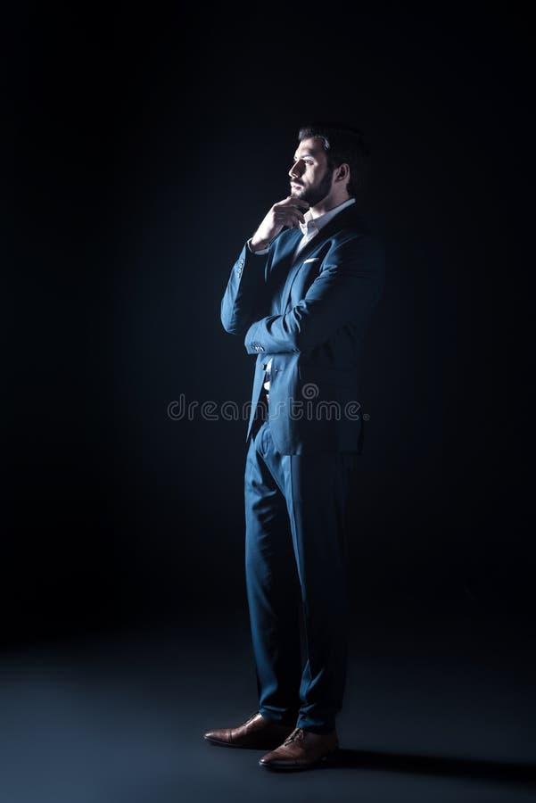 Ευφυής όμορφος επιχειρηματίας που στέκεται στο μαύρο κλίμα στοκ εικόνα