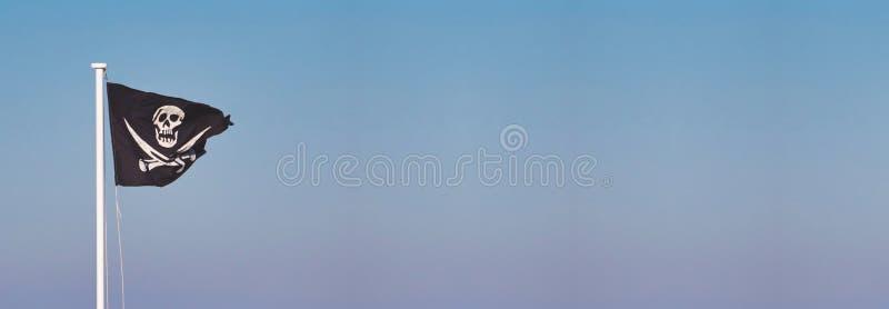 Ευχάριστα κρανίο και crossbones μαύρη σημαία του Ρότζερ σε έναν πόλο που κυματίζει στον αέρα στοκ εικόνα