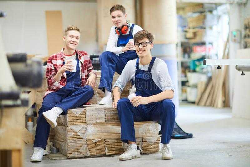 Ευχάριστα νέοι ξυλουργοί που χαλαρώνουν κατά τη διάρκεια του σπασίματος στοκ εικόνα με δικαίωμα ελεύθερης χρήσης