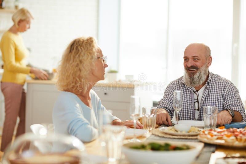 Ευχάριστα φίλοι που μιλούν περιμένοντας το γεύμα στοκ εικόνα με δικαίωμα ελεύθερης χρήσης