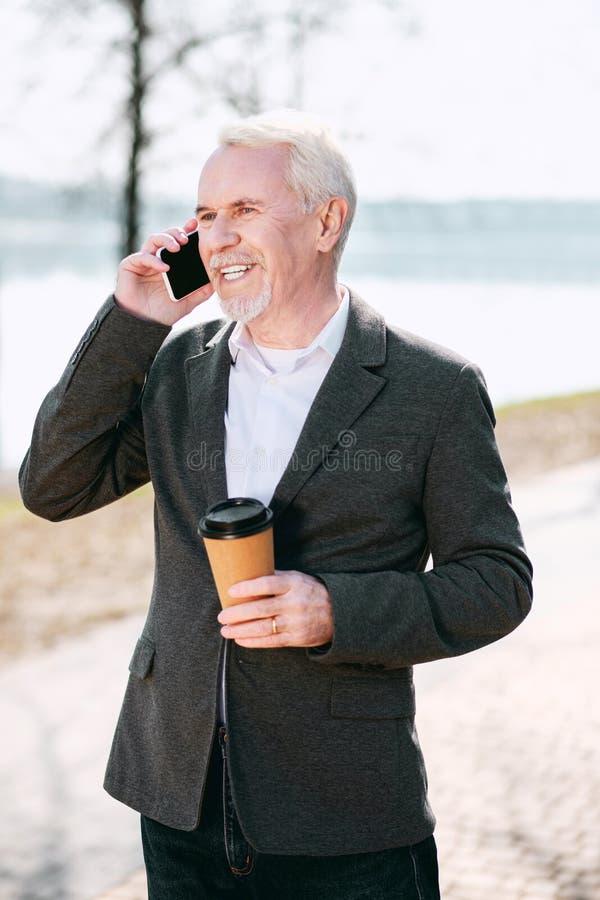 Ευχάριστα ώριμος καφές κατανάλωσης επιχειρηματιών στοκ φωτογραφία