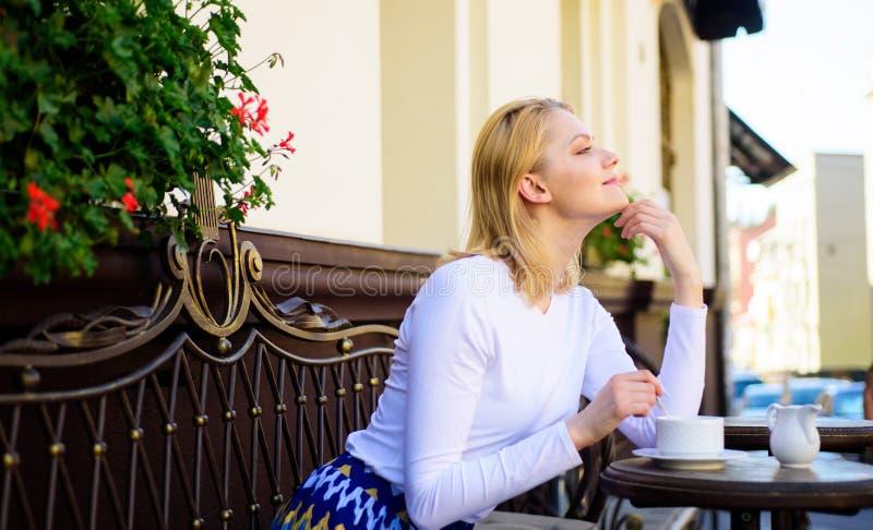 Ευχάριστες σκέψεις Απολαύστε τη ζωή της Το ξανθό ονειροπόλο πρόσωπο χαμόγελου γυναικών απολαμβάνει τον καφέ, το αστικό υπόβαθρο στοκ εικόνες με δικαίωμα ελεύθερης χρήσης