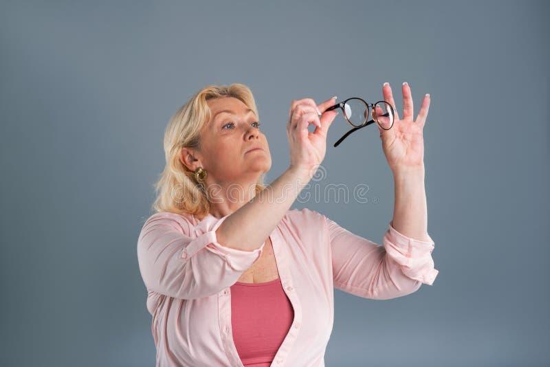Ευχάριστη ανώτερη γυναίκα που ελέγχει την καθαρότητα των γυαλιών στοκ εικόνες