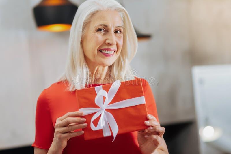 Ευχάριστη ανώτερη γυναίκα που κρατά ένα παρόν κιβώτιο στοκ εικόνα