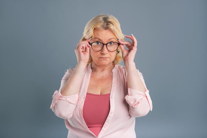 Ευχάριστη ανώτερη γυναίκα που προσπαθεί νέα eyeglasses στοκ εικόνα