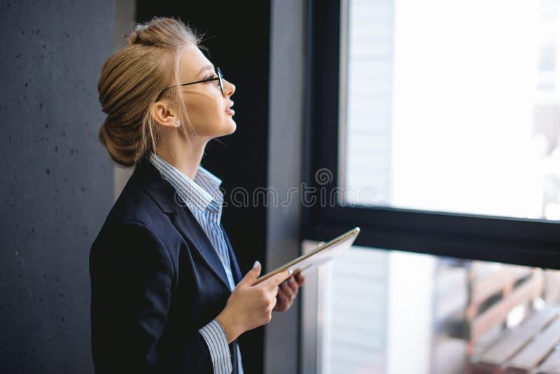 Ευχάριστη γυναίκα με τη δίκαιη τρίχα που κρατά το lap-top της και που εξετάζει το παράθυρο στοκ φωτογραφία