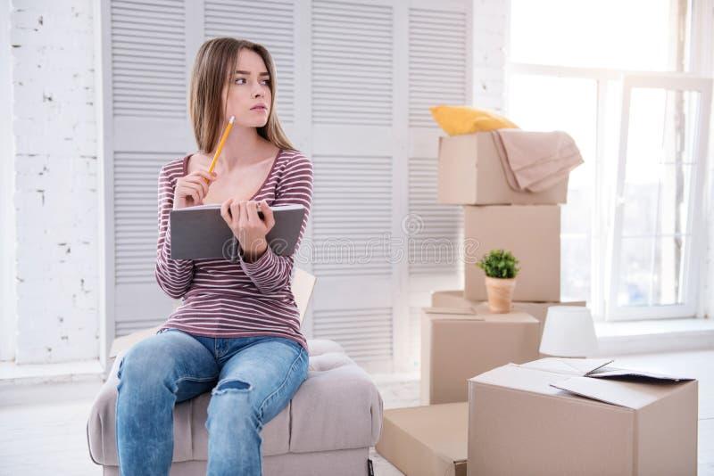 Ευχάριστη γυναίκα που ελέγχει τον κατάλογο στοιχείων πριν από να κινηθεί έξω στοκ εικόνες