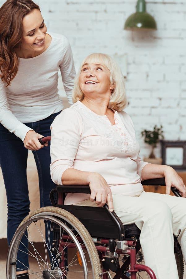 Ευχάριστη γυναίκα που φροντίζει τη γιαγιά της στην αναπηρική καρέκλα στοκ φωτογραφία