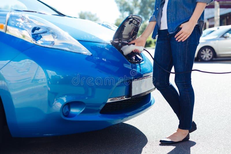 Ευχάριστη γυναίκα της Νίκαιας που συνδέει έναν ηλεκτρο φορτιστή με το αυτοκίνητο στοκ εικόνες