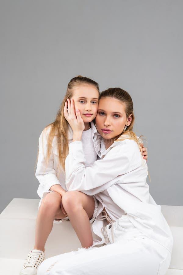 Ευχάριστη ενήλικη συνεδρίαση γυναικών με τη νεώτερη αδελφή της και ήπια σχετικά με στοκ εικόνες