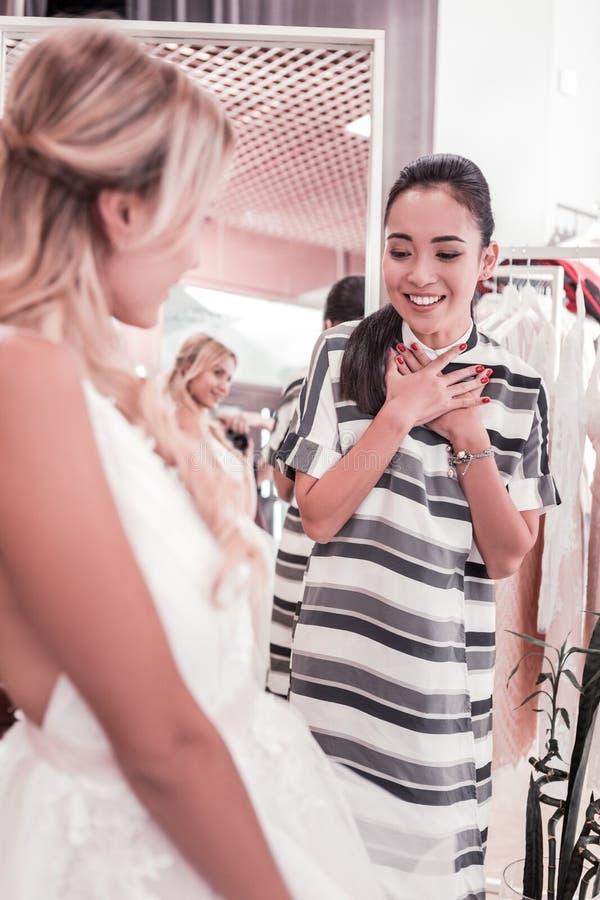 Ευχάριστη νέα γυναίκα που θαυμάζει το γαμήλιο φόρεμα στοκ εικόνα