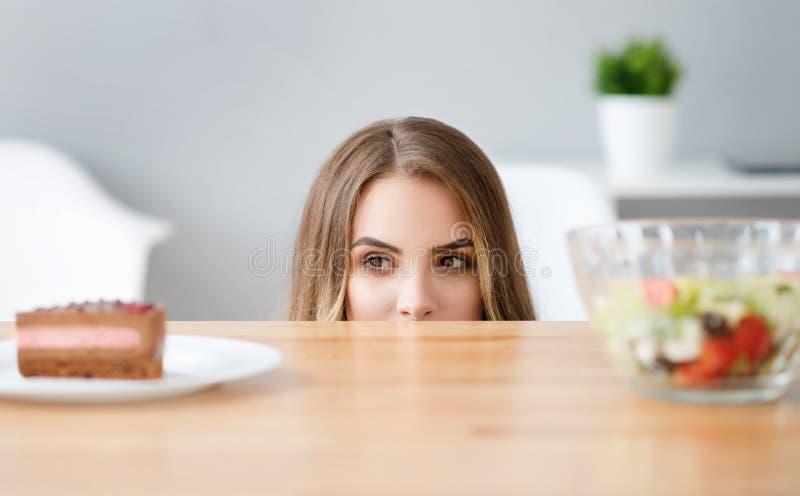 Ευχάριστη πανούργη γυναίκα που επιλέγει τι να φάει στοκ εικόνες
