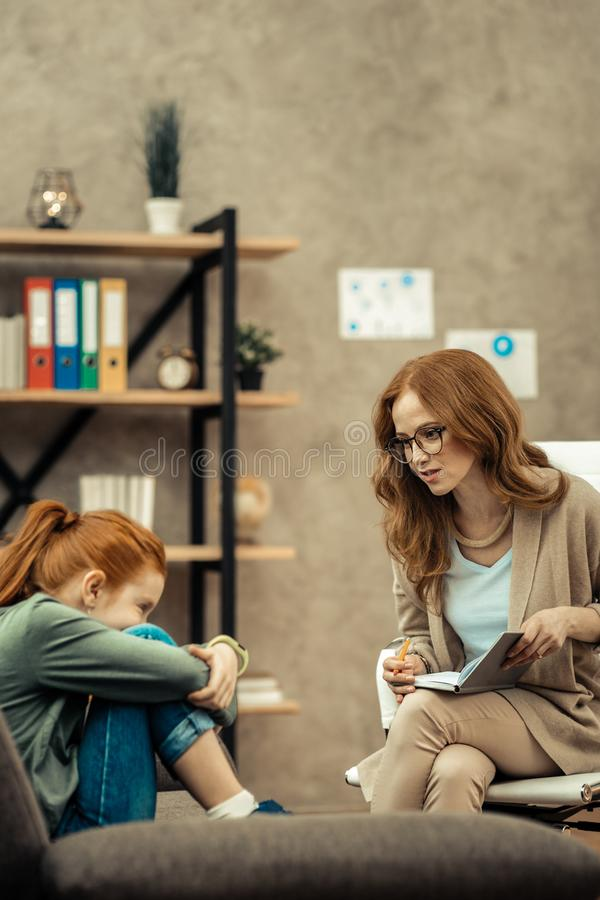Ευχάριστη όμορφη γυναίκα που μιλά με ένα χαριτωμένο κορίτσι στοκ εικόνες