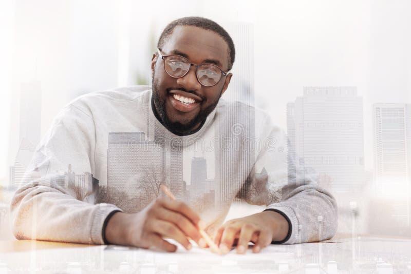Ευχάριστος αφροαμερικάνος που κάνει τα σχέδια στοκ εικόνες
