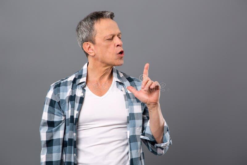 Ευχάριστο βάναυσο άτομο που εξετάζει το δάχτυλό του στοκ φωτογραφίες με δικαίωμα ελεύθερης χρήσης