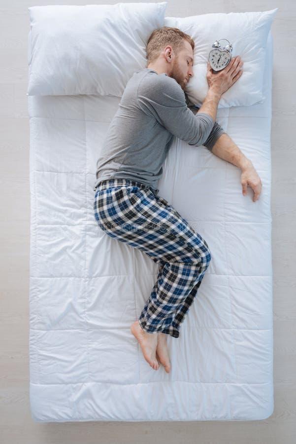 Ευχάριστο ειρηνικό άτομο που κρατά το ξυπνητήρι στοκ φωτογραφίες με δικαίωμα ελεύθερης χρήσης