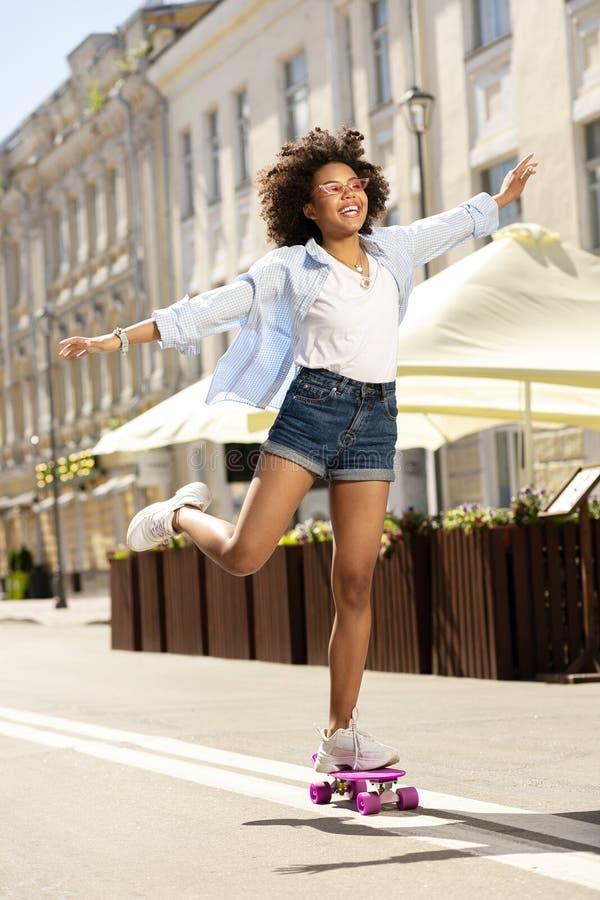 Ευχάριστο εύθυμο οδηγώντας skateboard κοριτσιών χαριτωμένα στοκ φωτογραφία