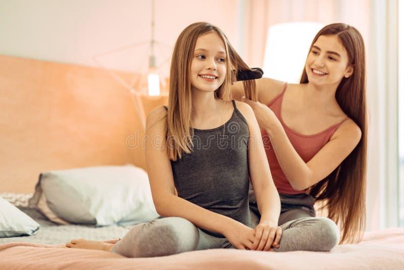Ευχάριστο κορίτσι που ισιώνει την τρίχα αδελφών της στοκ φωτογραφία με δικαίωμα ελεύθερης χρήσης
