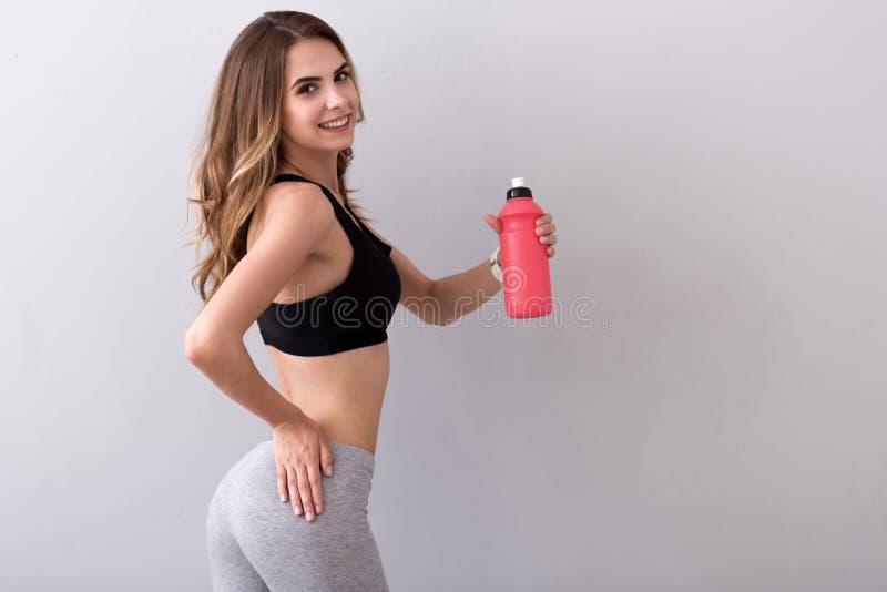 Ευχάριστο πόσιμο νερό γυναικών χαμόγελου στοκ εικόνες