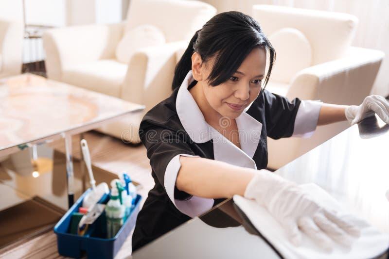 Ευχάριστο συμπαθητικό κορίτσι ξενοδοχείων που καθαρίζει το δωμάτιο ξενοδοχείου στοκ εικόνες με δικαίωμα ελεύθερης χρήσης