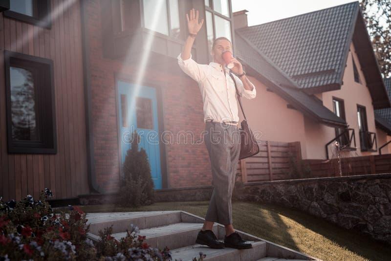 Ευχάριστο φιλικό άτομο που χαιρετά το γείτονά του αφήνοντας το σπίτι το πρωί στοκ φωτογραφία