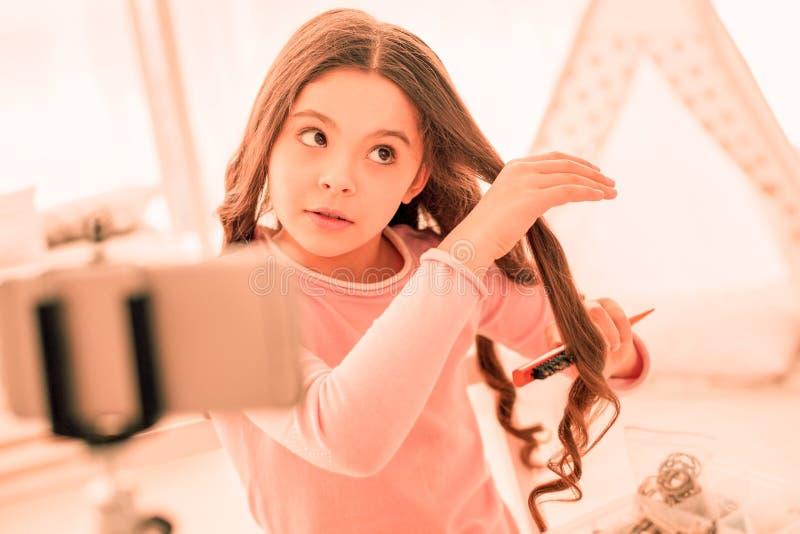Ευχάριστο χαριτωμένο κορίτσι που εξετάζει την τρίχα της στοκ εικόνα με δικαίωμα ελεύθερης χρήσης