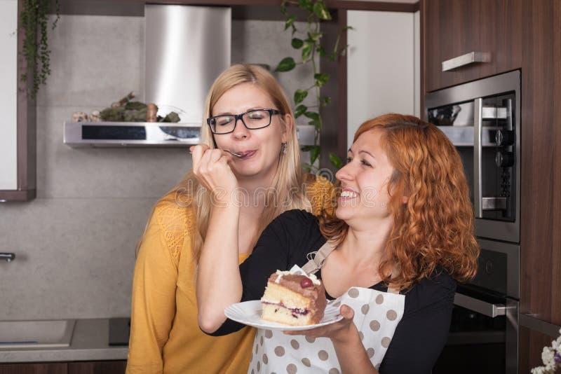 Ευχαριστημένες φίλες που τρώνε το κέικ στην κουζίνα στοκ εικόνες