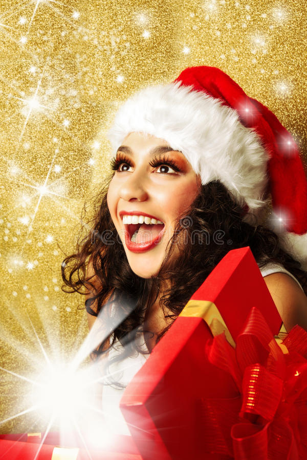 Ευχαριστημένη γυναίκα με το δώρο στο καπέλο Άγιου Βασίλη στοκ εικόνα με δικαίωμα ελεύθερης χρήσης