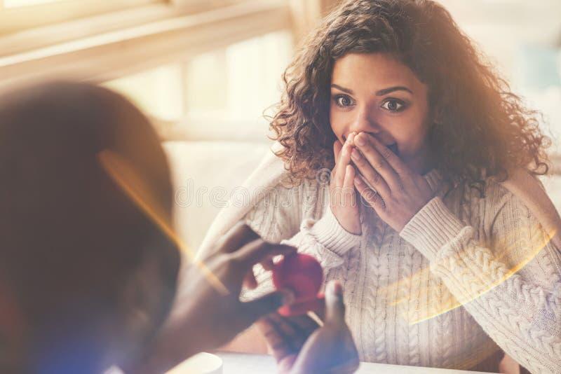 Ευχαριστημένη ευτυχής γυναίκα που εξετάζει το δαχτυλίδι αρραβώνων στοκ εικόνες