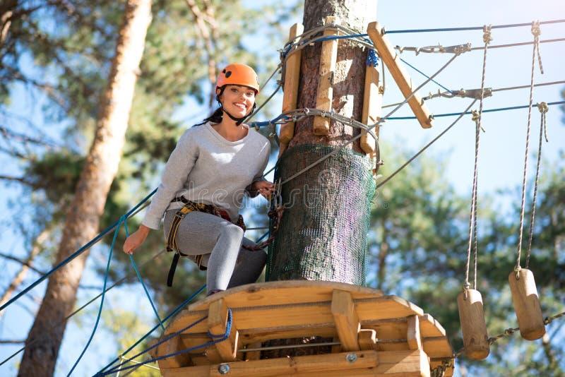 Ευχαριστημένη νέα γυναίκα που κάθεται οκλαδόν κοντά στο δέντρο στοκ εικόνες
