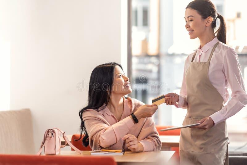 Ευχαριστημένη συμπαθητική σερβιτόρα που παίρνει μια πιστωτική κάρτα στοκ φωτογραφία