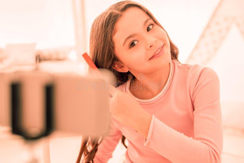 Ευχαριστημένο συμπαθητικό κορίτσι που κάνει ένα νέο hairstyle στοκ φωτογραφία με δικαίωμα ελεύθερης χρήσης