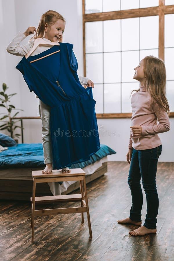 Ευχαριστημένο συμπαθητικό κορίτσι που κρατά ένα φόρεμα στοκ εικόνες
