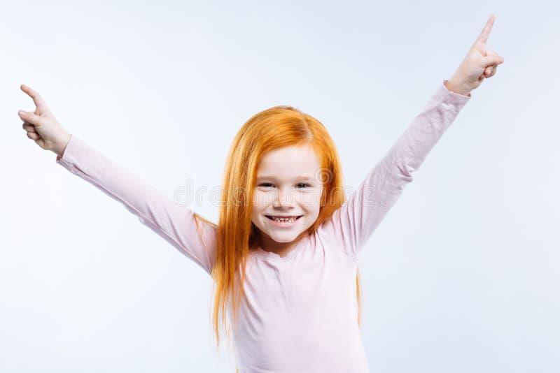 Ευχαριστημένο συμπαθητικό κορίτσι που στέκεται στο μπλε κλίμα στοκ εικόνες