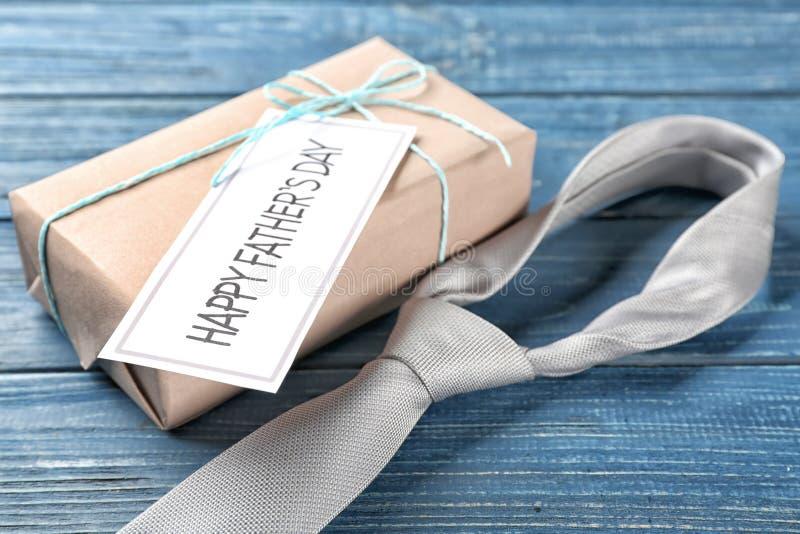 Ευχετήρια κάρτα για την ημέρα του πατέρα με το κιβώτιο δώρων και δεσμός στο ξύλινο υπόβαθρο στοκ εικόνα