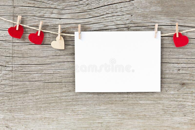 Ευχετήρια κάρτα και καρδιές ημέρας βαλεντίνων που κρεμούν σε ένα σκοινί στοκ εικόνες