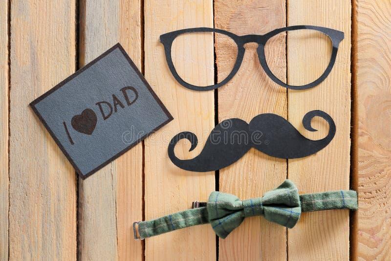 Ευχετήρια κάρτα με τη φράση Ι DAD ΑΓΑΠΗΣ, έγγραφο mustache, γυαλιά και δεσμός τόξων στο ξύλινο υπόβαθρο Εορτασμός ημέρας πατέρα στοκ εικόνες