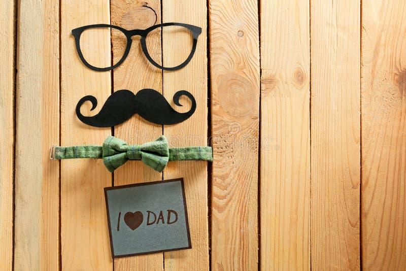 Ευχετήρια κάρτα με το DAD ΑΓΆΠΗΣ φράσης \ «Ι \», έγγραφο mustache, γυαλιά και δεσμός τόξων στο ξύλινο υπόβαθρο Εορτασμός ημέρας π στοκ φωτογραφία με δικαίωμα ελεύθερης χρήσης