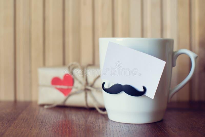 Ευχετήρια κάρτα στο φλυτζάνι με το αστείο mustache πέρα από τον ξύλινο πίνακα r E r Πρότυπο στοκ φωτογραφίες